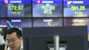 A currency trader watches monitors at the foreign exchange dealing room of the KEB Hana Bank headquarters in Seoul (AP Photo/Ahn Young-joon)