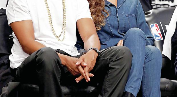 Jay Z and his wife Beyonce look relaxed at a baseball game in New York hours after the CCTV footage appeared