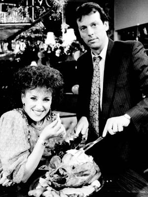 EastEnders' Dennis Watts (Leslie Grantham) with screen wife Angie (Anita Dobson) carving the Christmas turkey (PA)