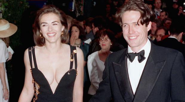 Hugh Grant and then girlfriend Liz Hurley (Michael Stephens/PA) revealing Versace evening dress. *27/4/99 Hollywood superstar Julia Roberts jetted into Britain to the premiere of her latest movie, Notting Hill, but was upstaged by co-star Hugh Grant's girlfriend Liz Hurley and her dazzling dress. Model Hurley, the face of Estee Lauder, repeated the same trick she pulled off five years ago for the launch of Four Weddings And A Funeral when she wore a stunning Versace frock. For Notting Hill, the follow up to Four Weddings, she turned heads in a sheer and shimmering backless outfit, which was split from ankle to thigh and was again Versace.