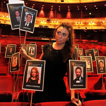 Rosie Wiseman places photos of Actors and Actresses on the seats of the stalls, where this years annual BAFTA ( British Academy of Film and Television Arts) will be held this coming Sunday, at the Royal Opera house in Covent Garden central London. PRESS ASSOCIATION Photo. Picture date: Wednesday February 6, 2013. Photo credit should read: John Stillwell/PA Wire