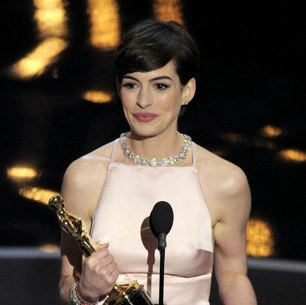 Anne Hathaway accepts the award for best actress in a supporting role for