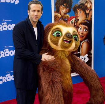 Ryan Reynolds poses with Belt the sloth at The Croods premiere in New York