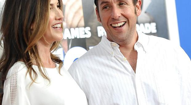 Actor Adam Sandler attends the premiere of Grown Ups 2 in New York with his wife Jackie