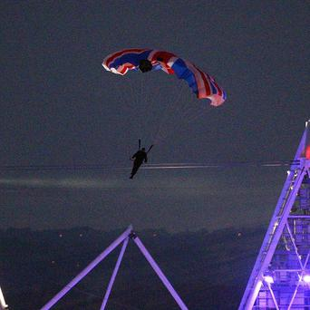 Stuntman Mark Sutton parachuted into the Olympic Stadium dressed as James Bond
