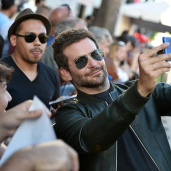 Bradley Cooper takes a selfie with a fan at the premiere of Guardians Of The Galaxy in Los Angeles