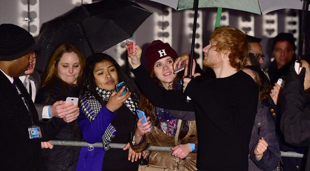 Ed Sheeran takes selfies with fans at the BBC Music Awards at Earl's Court, London.