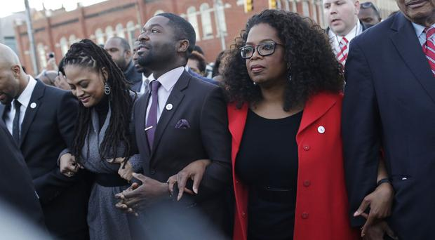 Oprah Winfrey locks arms with Selma co-star David Oyelowo as they march to the Edmund Pettus Bridge in honour of Martin Luther King Jr