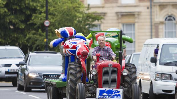 Nick Park, creator of Shaun the Sheep driving a vintage tractor with a trailer load of Shaun the sheep sculptures across the Clifton suspension bridge, Bristol.