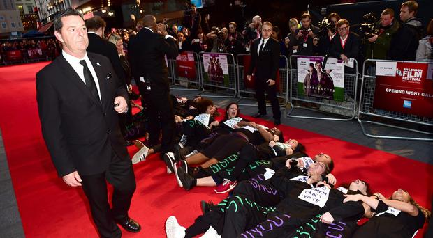Protesters lie on the red carpet during the Suffragette premiere held during the 59th BFI London Film Festival at Odeon Cinema at Leicester Square
