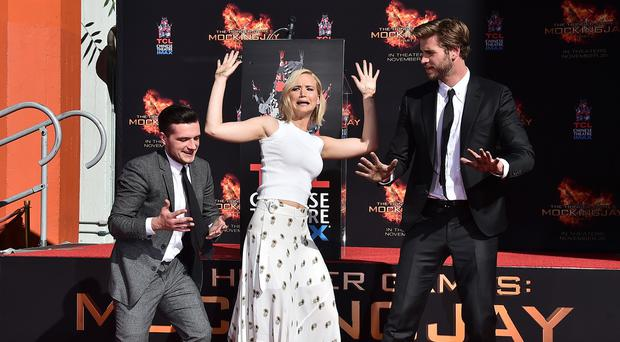 Josh Hutcherson, Jennifer Lawrence and Liam Hemsworth show off their hands after placing them in cement in LA (AP)