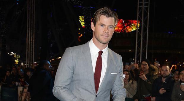 Chris Hemsworth walks the blue carpet at the premiere for In The Heart Of The Sea