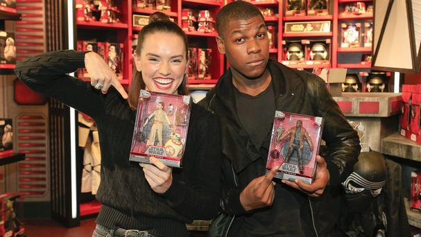 Daisy Ridley and John Boyega with their Star Wars characters' action figures at the Disney store in London
