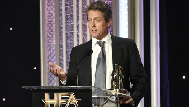 Hugh Grant accepts his supporting actor award (Invision/AP)