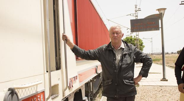 Chris Tarrant stands in front of a train