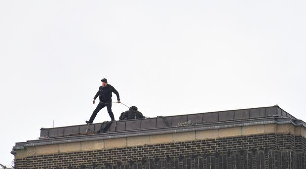 Tom Cruise prepares to run towards a helicopter on the chimney top of the Tate Modern gallery in London