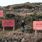 John Bhaba Jeaic O Conghaile with three billboards he erected to honour Martin McDonagh (Niall Carson/PA)