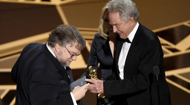 Guillermo del Toro checks the winning envelope (Chris Pizzello/AP)