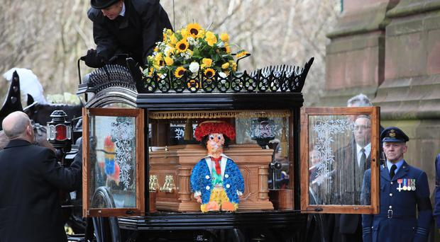 The funeral cortege arrives at Liverpool Anglican Cathedral with a floral tribute of a DiddyMan (Peter Byrne/PA)