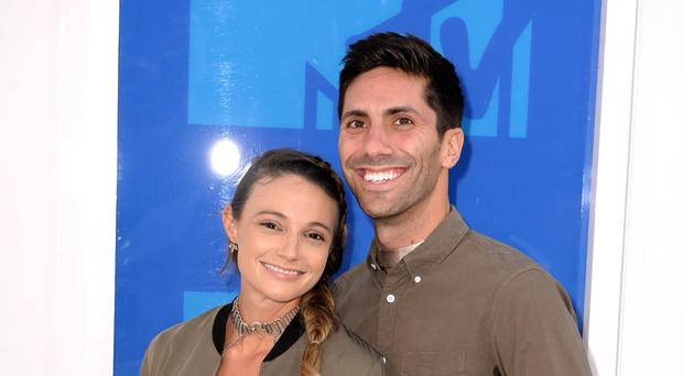 MTV has suspended production of Catfish, amid allegations of sexual misconduct involving host Nev Schulman, who is pictured here with his partner Laura Perlongo (PA)