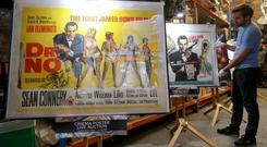 A poster for the 1962 Bond film Dr No alongside a poster for the 1963 James Bond film From Russia with Love, adjusted by Prop Store employee Matt Storey (Andrew Matthews/PA Wire)