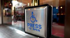File photo dated 15/09/14 of a disabled entrance door button. The Government is being urged to make firms publish their disability pay gaps after new research suggested the difference with other workers has hit more than £2,800 a year.