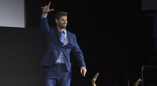 Chris Hemsworth gestures to fans as he walks on stage during Marvel Studios' Comic-Con panel (Chris Pizzello/Invision/AP)