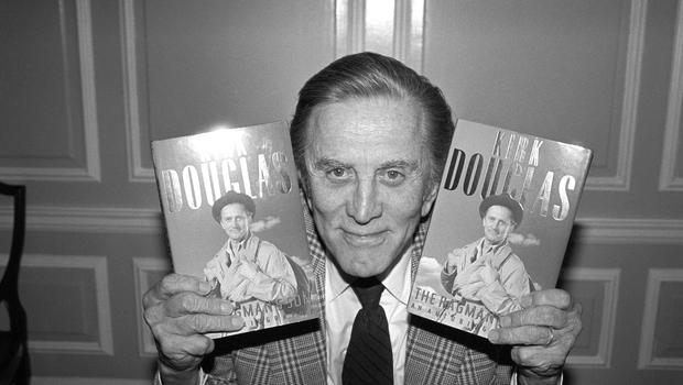 Hollywood actor Kirk Douglas posing with copies of his autobiography The Ragman's Son (PA)