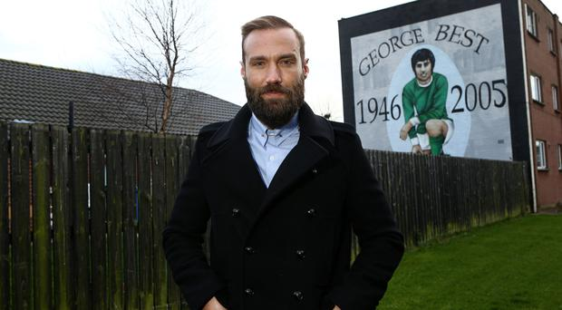 Calum Best in front of mural honouring his famous father in the Cregagh estate