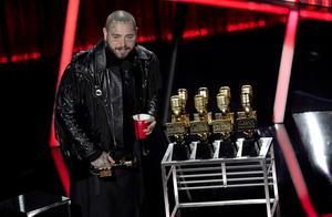 Post Malone took home nine awards on the night, including the biggest prize, top artist. He proudly posed with his golden trophies (AP Photo/Chris Pizzello)