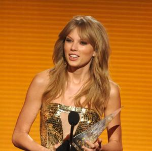 Taylor Swift accepts one of her three awards at the American Music Awards (John Shearer/Invision/AP)