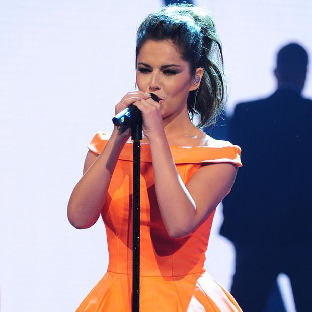 Cheryl Cole showed off a new tattoo as she took to the stage with Girls Aloud