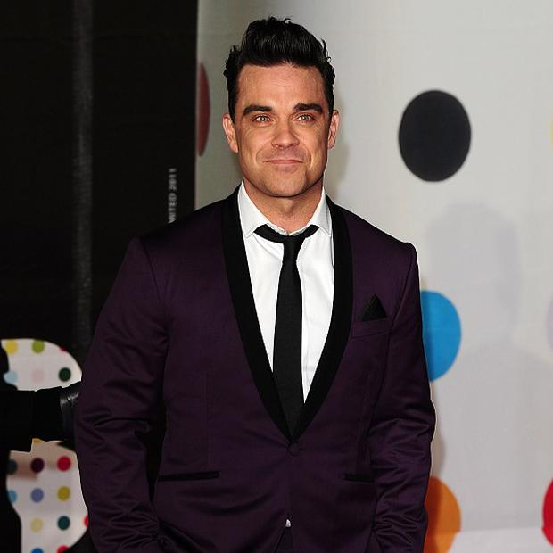 Robbie Williams is reportedly going to sing at his dad's wedding