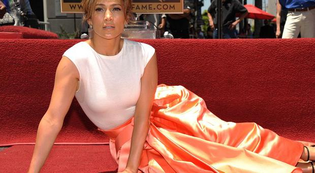 Jennifer Lopez poses with her star on the Hollywood Walk of Fame
