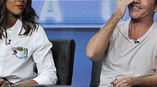 Simon Cowell reacts to a reporter's question as fellow X Factor judge Kelly Rowland looks on (AP)