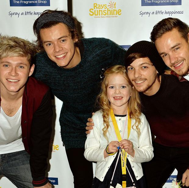 Four members of the boy band One Direction with fan Livvie Ellis