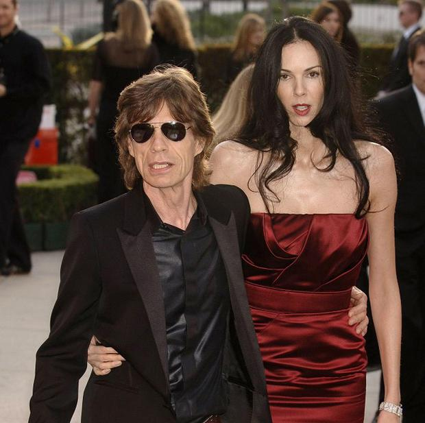 Sir Mick Jagger has arrived in LA to arrange L'Wren Scott's funeral, with the support of his children