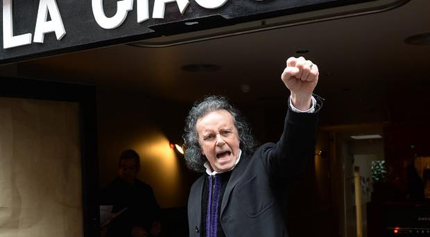 60's pop singer, Donovan performs a song outside the Giaconda Cafe in Denmark Street in London, also known as 'Tin Pan Alley'