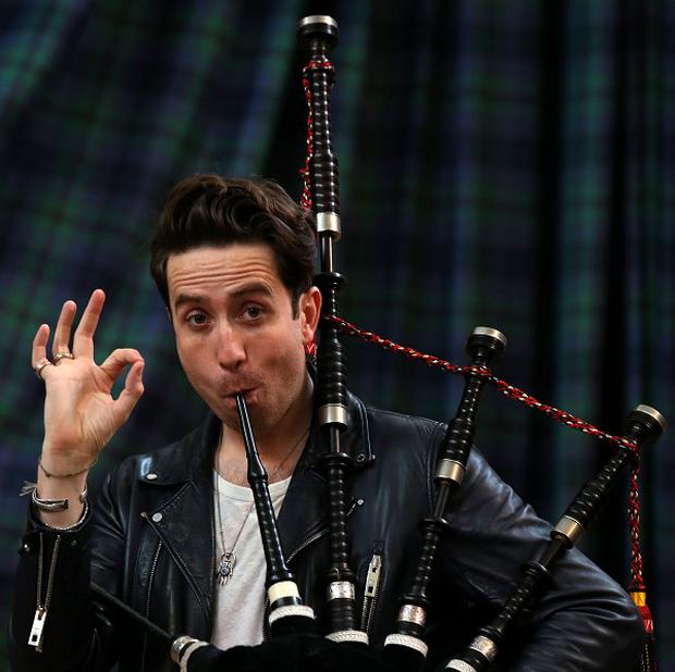 Radio 1 breakfast show host Nick Grimshaw is taught how to play the bagpipes at The National Piping Centre in Glasgow by Finlay MacDonald ahead of the Radio 1 Big weekend