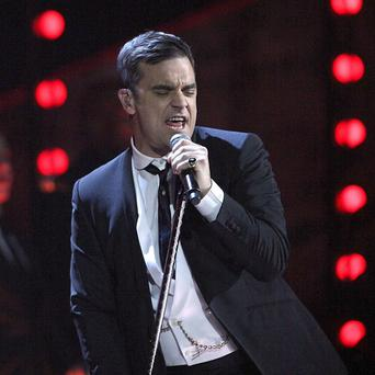 Robbie Williams reportedly injured a fan when he fell off stage