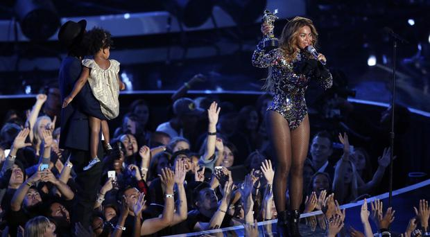 Beyonce accepts the Video Vanguard Award with Blue Ivy and Jay-Z at left during the MTV Video Music Awards (AP)