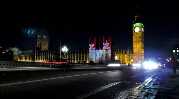 The official video for the Band Aid 30 charity single is projected onto the Houses of Parliament