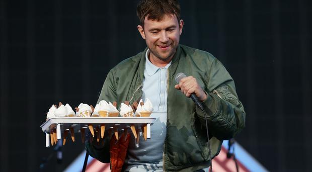 Damon Albarn hands out ice cream to the crowd during Blur's performance