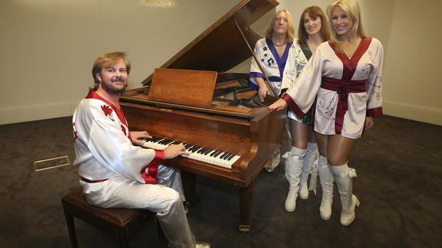 Tribute band Bjorn Again with ABBA's Bolin grand piano, which is being auctioned at Sotheby's