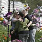 Prince fans embrace by a makeshift memorial outside Paisley Park, the home of the singer, in Chanhassen, Minnesota (AP)