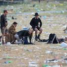 Festival goers sit amongst rubbish following the Glastonbury Festival at Worthy Farm in Pilton, Somerset (Ben Birchall/PA)