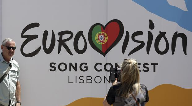 A fan takes a picture in front of a banner at the Eurovision Song Contest in Portugal (Armando Franca/AP)