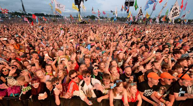 Festivalgoers watch the Pyramid Stage at Glastonbury Festival (Ben Birchall/PA)