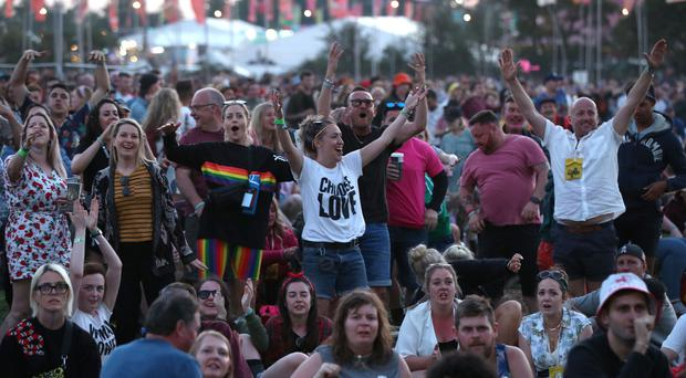 Festival-goers watch the England World Cup match on a big screen at Glastonbury Festival (Yui Mok/PA)