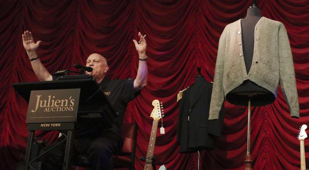 Auctioneer Deninis Kruse for Julien's Auctions with Kurt Cobain sweater and guitar (David Willems/PA)